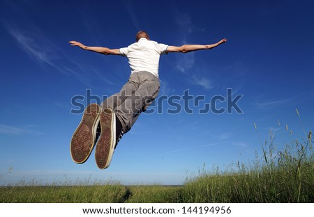 Man jumping on the grass field - stock photo