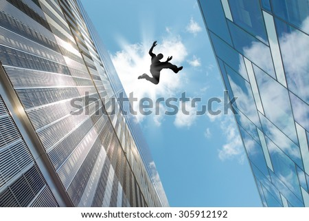 Man jumping over building roof against blue sky background - stock photo