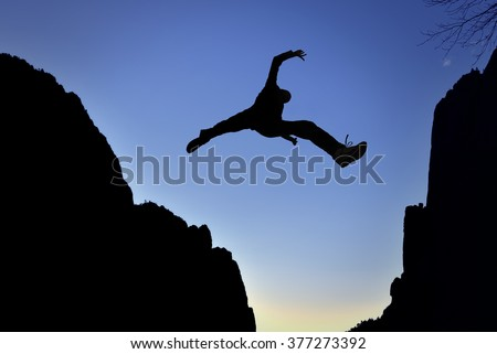 Man jumping over precipice between two mountains - stock photo