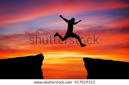 Man jumping over rocks with gap on sunset fiery background.