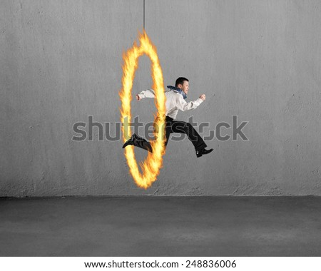 Man jumping through fire hoop with concrete wall background - stock photo