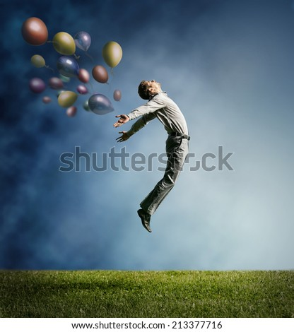 Man jumping up to Sky wit color bright balloon - stock photo
