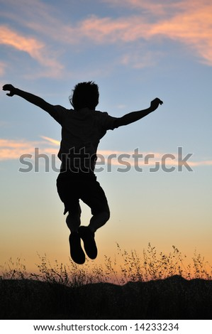 Man jumps above tall grasses in front of a fiery sunset. - stock photo
