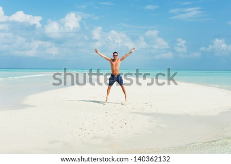 Man jumps on the background of beautiful beach with white sand and cloudy sky - stock photo