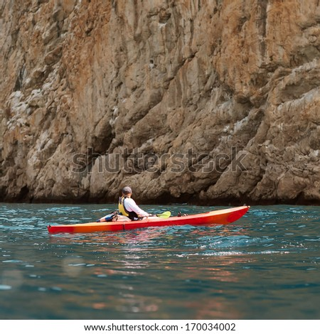 man kayak in the ocean of mountains - stock photo