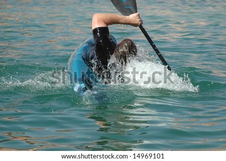 Man kayaking doing eskimo roll - stock photo