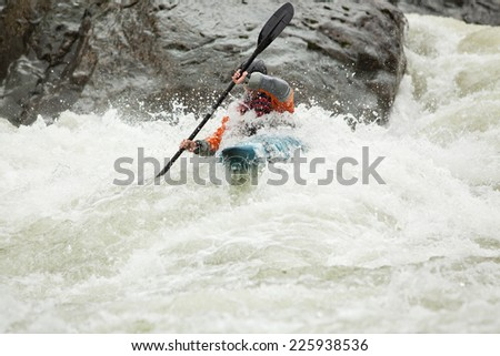 Man kayaking down a section of whitewater on the Skykomish River in Washington State.