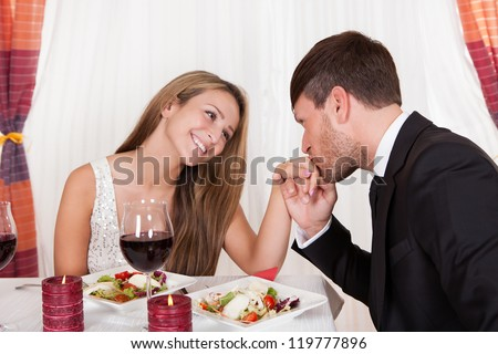 Man kissing a woman's hand at a romantic dinner as she looks at him with an adoring expression and lovely smile - stock photo