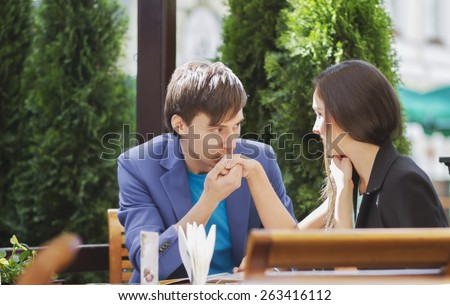Man kissing a woman's hand at a summer cafe - stock photo
