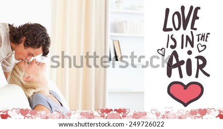 Man kissing his girlfriend on the forehead against love is in the air - stock photo