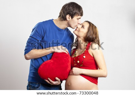 Man kissing his pregnant wife's nose holding red heart at hands