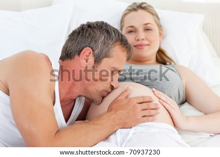Man kissing his wife's belly at home - stock photo