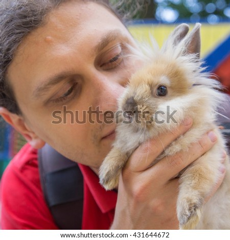 Man kissing the baby rabbit. Animal care concept