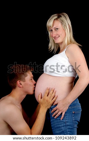Man kissing the stomach of his pregnant wife