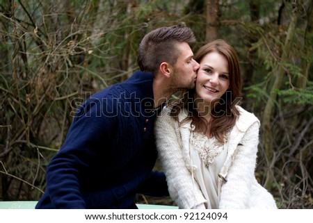 Man kissing woman on the cheek in the forest in front of trees - stock photo