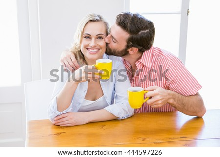 Man kissing woman while having coffee at home