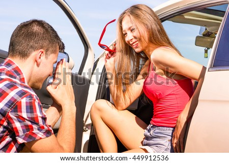 Man kneeling down beg forgiveness at girlfriend inside car - Beautiful girl smiling at guy marriage proposal - Concept of holiday couple situation with peaceful reconciliation - Soft vintage filter - stock photo