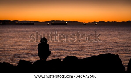 Man kneeling down beside the ocean, looking out at the horizon.  - stock photo