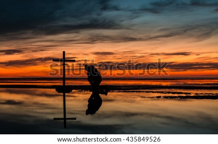 Man kneeling in prayer by a black cross with a very warm Sunset sky behind him. - stock photo