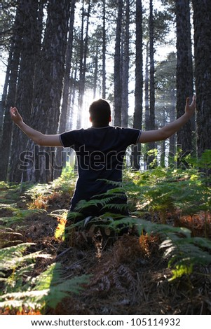 Man Kneeling in the forest with arms lifted up - stock photo