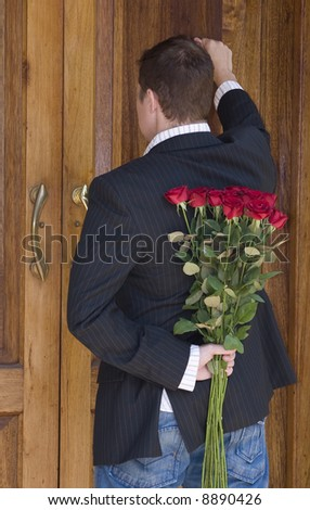 Man knocking on door to present flowers to his date on valentines day - stock photo