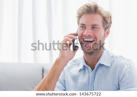 Man laughing while he is on the phone sat on a couch
