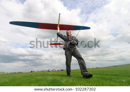 Man launches into the sky RC glider, wide-angle - stock photo