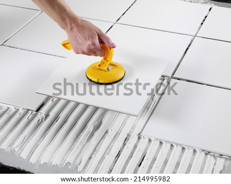 MAN LAYING CERAMIC FLOOR TILES - stock photo