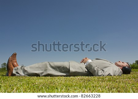 Man laying down in park listening to headphones - stock photo