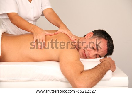 Man laying on massage bed - stock photo