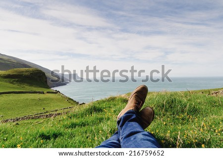 Man laying on the ground in a grass field, resting on a hill in the County Antrim, Northern Ireland - stock photo