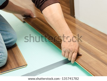 Man laying parquet in clean room while sitting on knees - stock photo