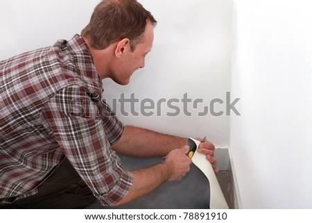 Man laying pvc floor - stock photo