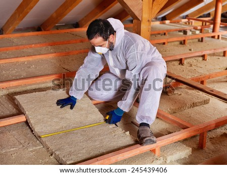 Man laying thermal insulation layer under the roof - measuring a mineral wool panel - stock photo