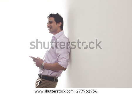 Man leaning against a wall smiling - stock photo