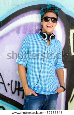 Man leaning against graffiti wall - stock photo
