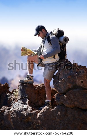Man leaning on a rock with a compass and a plan - stock photo