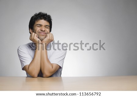 Man leaning on elbows and making a face - stock photo