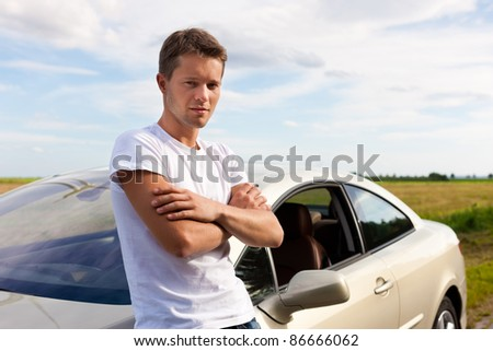 Man leaning on his car; presumably he has a break from driving - stock photo
