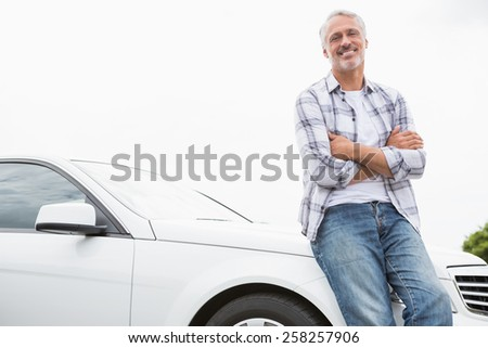 Man leaning on the bonnet of his car - stock photo