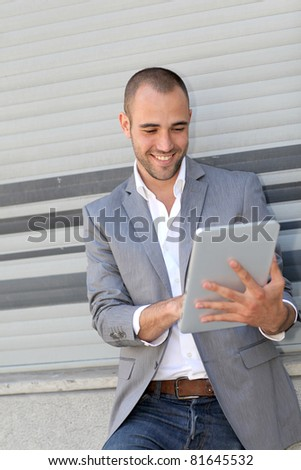 Man leaning on wall with electronic tablet - stock photo