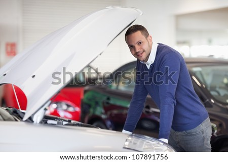 Man leaning over a car in a dealership
