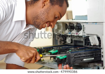 Man leaning over open photocopier during maintenance repairs using handheld tool, black mechanical parts