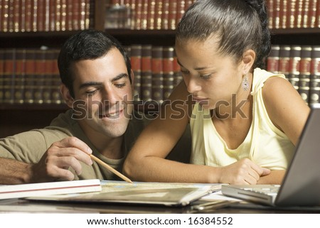 Man leans down next to woman. She is seated at table and he is helping her study. Horizontally framed photo. - stock photo