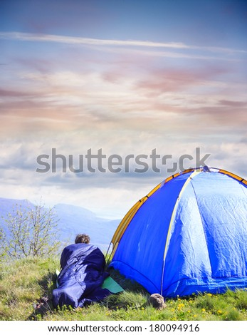 Man lie in sleeping bag near the tent - stock photo