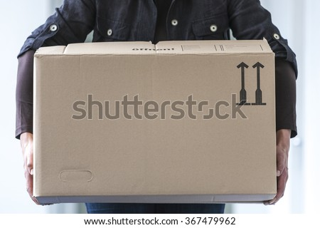 Man lifting a cardboard box, close-up