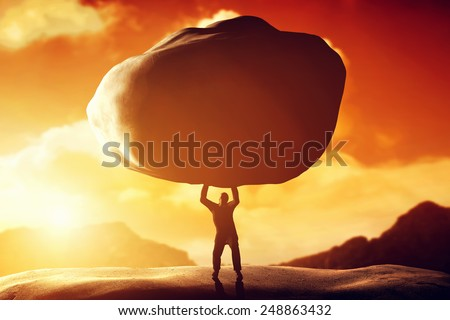 Man lifting a huge rock. Metaphor, concept of strength, burden, ballast, power etc. - stock photo