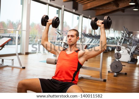 Man lifting dumbbells in a fitness club - stock photo