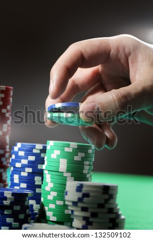 Man lifting two gambling chips from stacks with his hand.