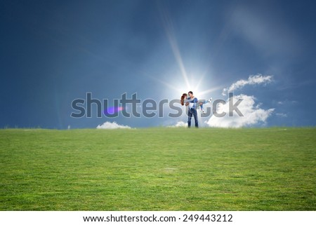 Man lifting up his girlfriend against cloudy sky with sunshine - stock photo